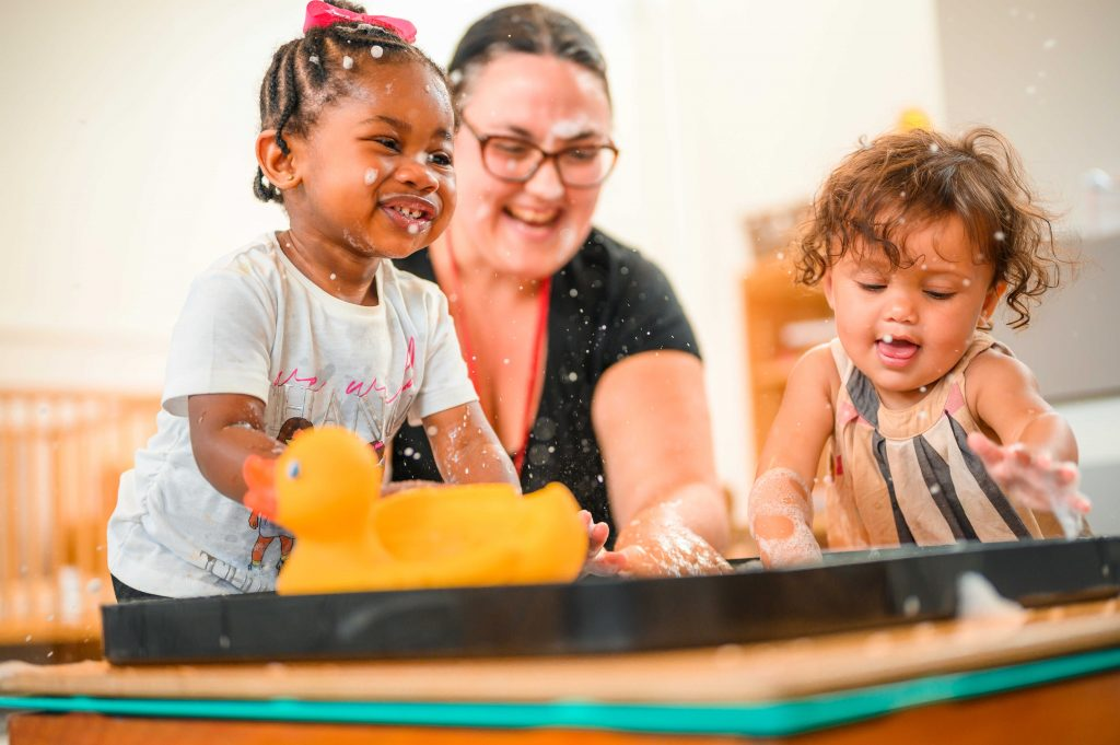 Nursery worker and two toddlers playing with bubbles and a bath duck