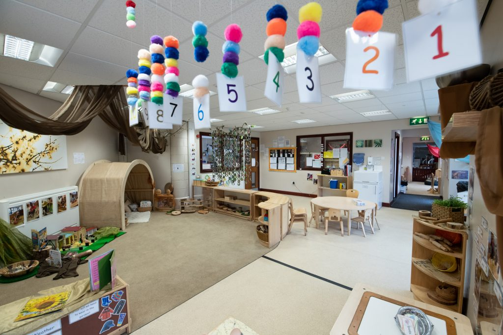 Children's play area with hanging pompoms and numbers