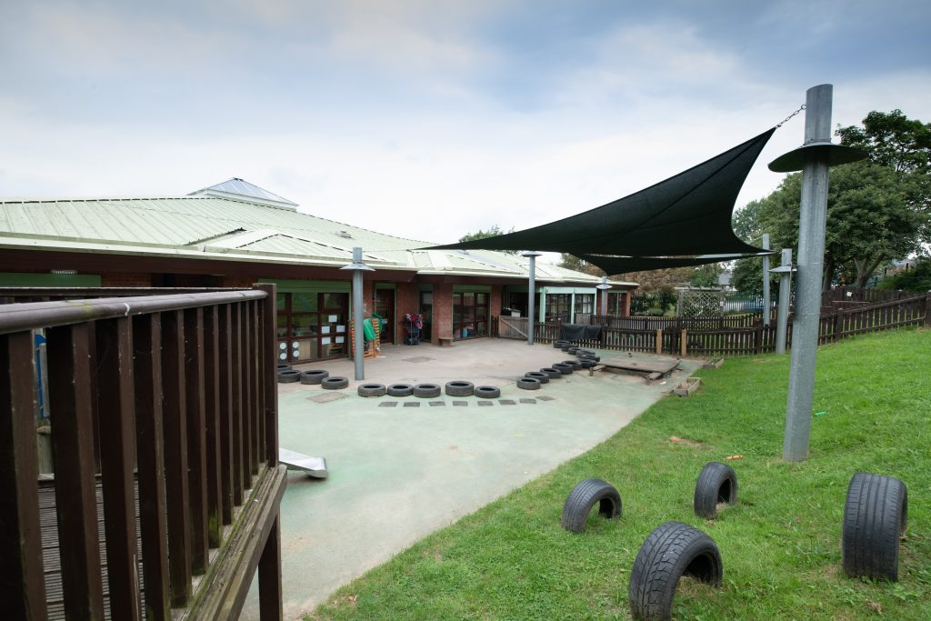Nursery exterior with play area and grass with tires